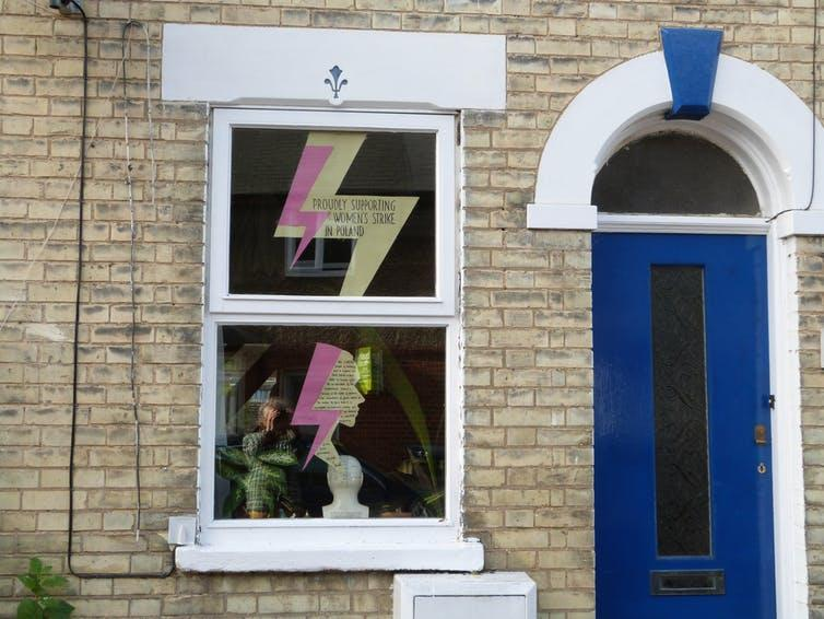 A lightning bolt sign in the window of a terraced house.