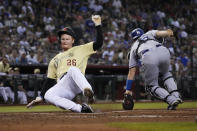 Arizona Diamondbacks' Pavin Smith (26) scores a run behind Los Angeles Dodgers catcher Will Smith on a ball hit by Josh VanMeter in the fifth inning during a baseball game, Friday, Sept. 24, 2021, in Phoenix. (AP Photo/Rick Scuteri)