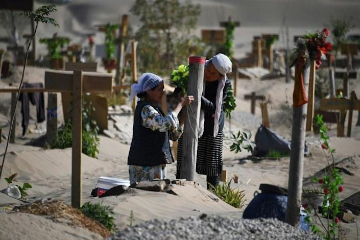 Two women decorate a grave in a Uighur graveyard on the outskirts of Hotan in China's northwestern Xinjiang region in May 2019 (AFP Photo/Greg Baker)
