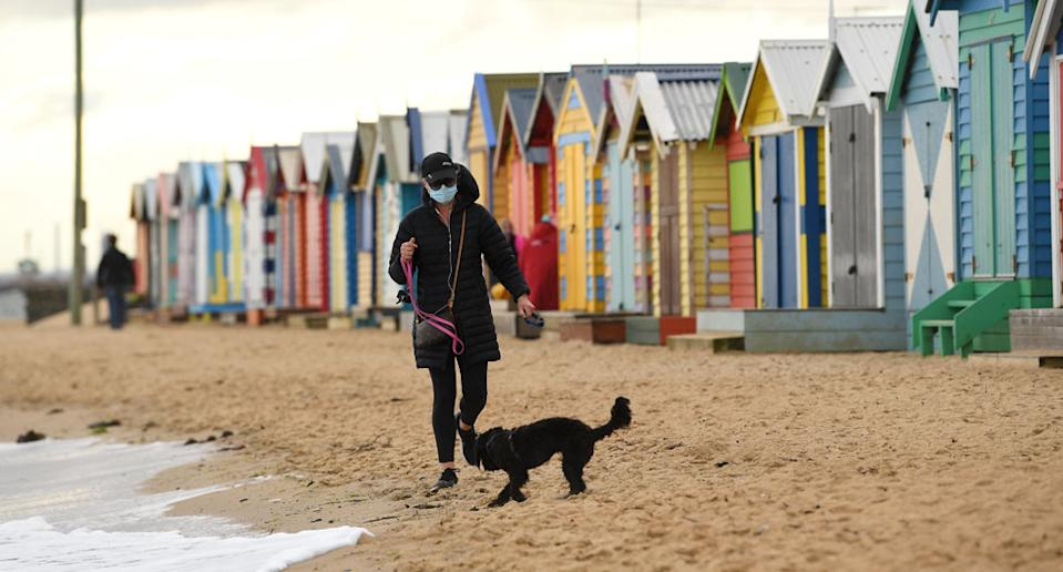 A person wearing a face mask is seen walking their dog along Brighton beach in Melbourne. Source: AAP/James Ross