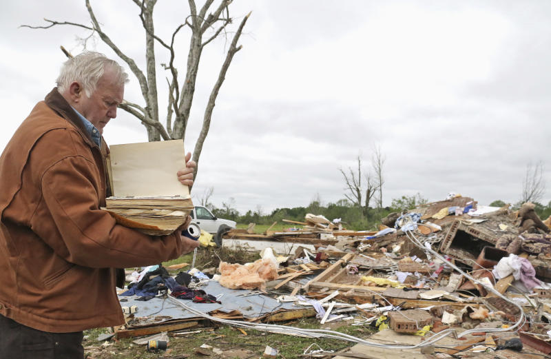 Robert Scott looks through a family Bible that he pulled out of the rubble after a tornado touched down near Hamilton, Mississippi on Sunday. (ASSOCIATED PRESS)