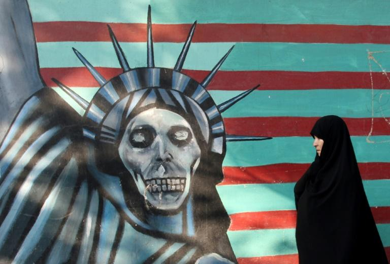 An Iranian woman walks past a mural on the wall of the former US embassy in TehranMore