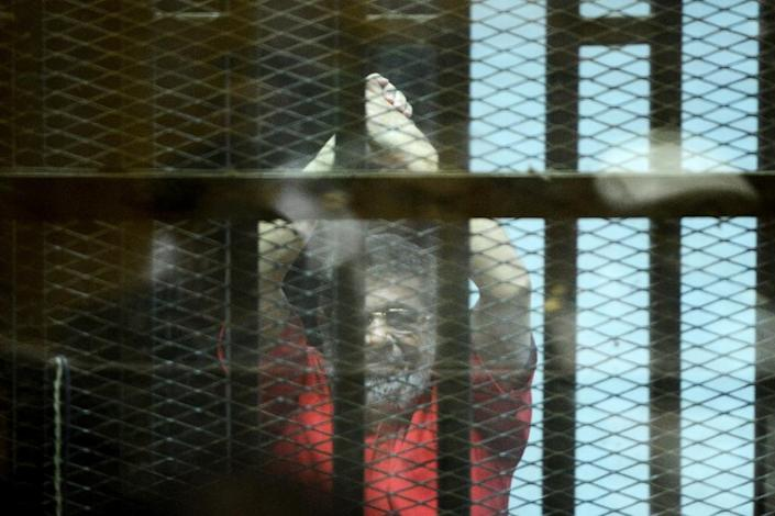 Egypt's ousted Islamist president Mohamed Morsi gestures from behind bars during his June 2016 trial (AFP Photo/MOHAMED EL-SHAHED)
