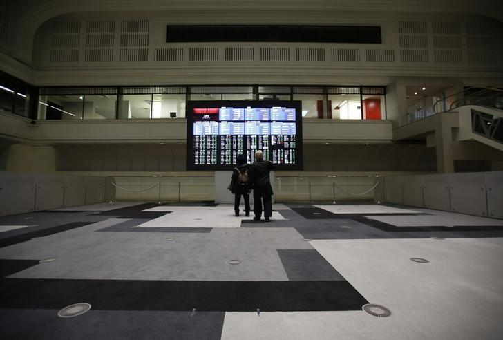 Visitors looks at an electronic board showing the Japan's Nikkei average at the Tokyo Stock Exchange in Tokyo