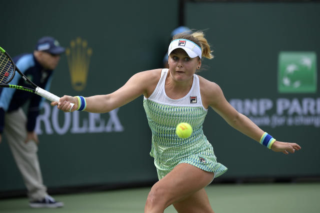 Kateryna Kozlova, of Ukraine, returns to Simona Halep, of Romania, at the BNP Paribas Open tennis tournament Sunday, March 10, 2019, in Indian Wells, Calif. (AP Photo/Mark J. Terrill)