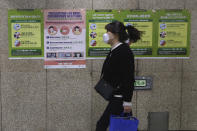 A woman wearing a face mask passes by posters about precautions against new coronavirus at a subway station in Seoul, South Korea, Saturday, March 21, 2020. For most people, the new coronavirus causes only mild or moderate symptoms, such as fever and cough. For some, especially older adults and people with existing health problems, it can cause more severe illness, including pneumonia. (AP Photo/Ahn Young-joon)
