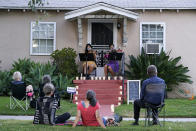 Nancy Kuo, top left, and Manoela Wunder, of the musical duo Masked Strings, perform a concert for their neighborhood, Sunday, Aug. 30, 2020, in the Atwater Village section of Los Angeles. Kuo and Wunder have been performing as the Masked Strings since May, and perform socially distanced events in addition to their own concerts, since the coronavirus pandemic has prevented them from getting regular music gigs. (AP Photo/Chris Pizzello)