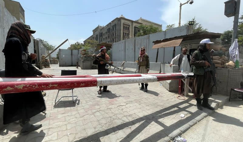 Members of Taliban forces keep watch at a check point in Kabul