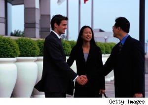 two men shake hands as woman looks on