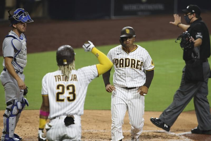 San Diego Padres' Trent Grisham, second from right, reacts after hitting a solo home run off Los Angeles Dodgers starting pitcher Clayton Kershaw in the sixth inning of a baseball game Monday, Sept. 14, 2020, in San Diego. (AP Photo/Derrick Tuskan)