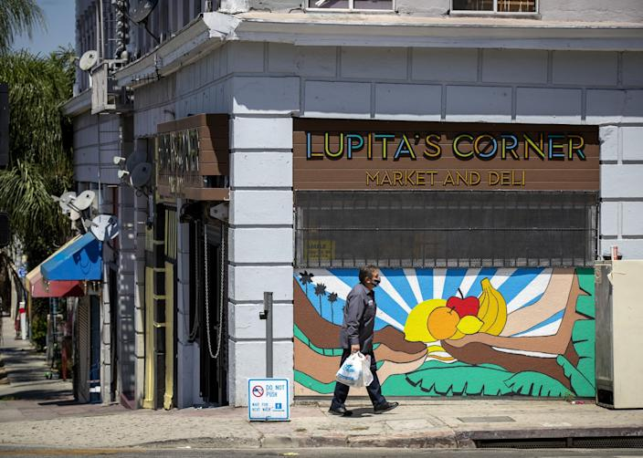 "A man carries a bag of food past a mural at Lupita's Corner Market And Deli, a family-owned business in L.A.'s Westlake District for nearly 30 years. <span class=""copyright"">(Allen J. Schaben/Los Angeles Times)</span>"