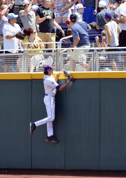 LSU right fielder Mark Laird climbs the wall to see a two-run home run hit by North Carolina's Brian Holberton land in the stands in the first inning of an NCAA College World Series elimination baseball game in Omaha, Neb., Tuesday, June 18, 2013. (AP Photo/Ted Kirk)