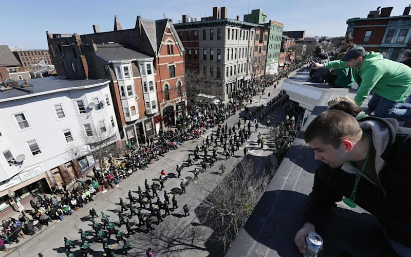 People watch the annual St. Patrick's Day parade from a roof in Boston - Credit: Michael Dwyer/AP