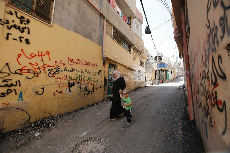 Palestinians walk past graffiti in the Dheisheh Refugee Camp near the West Bank town of Bethlehem on May 14, 2017