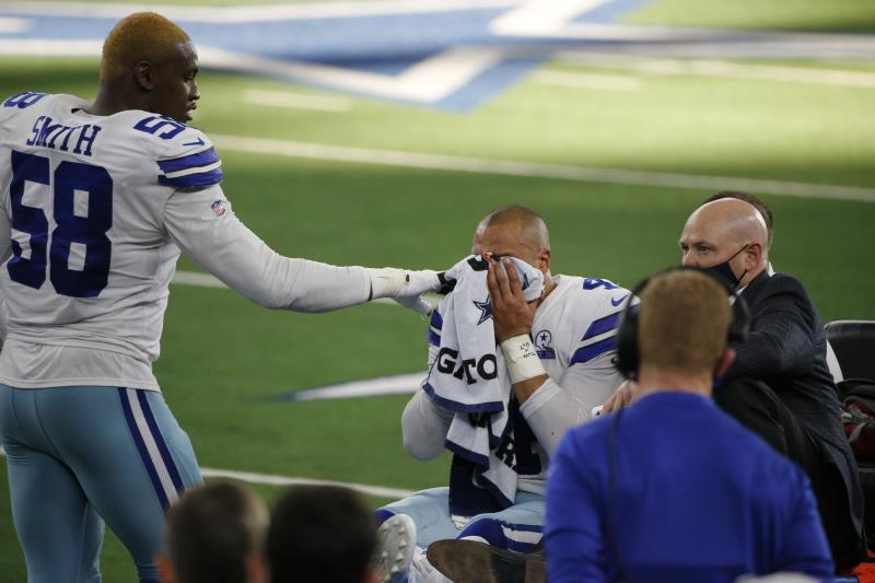 Aldon Smith pats Dak Prescott on the shoulder as Prescott covers his face with a towel.