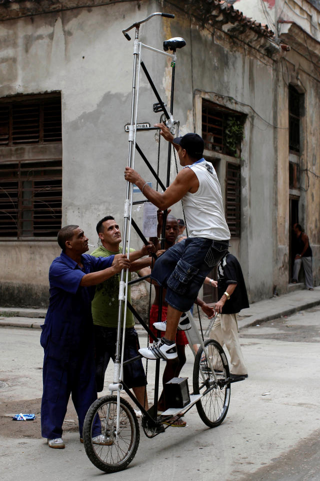 n this May 18, 2012 file photo, Felix Guirola climbs up his self-made 3.45 meters (11 feet) tall bicycle as people help steady it as he prepares to take it for a ride in Havana, Cuba. Guirola has been riding tall since 1983, when seeing a tandem bike inspired him to build up instead of out. He said his first tall bike measured 5.3 feet (1.6 meters), and they got progressively taller until five years later he was riding 18 feet (5.5 meters) in the air at Ciego de Avila carnivals. (AP Photo/Franklin Reyes, File)