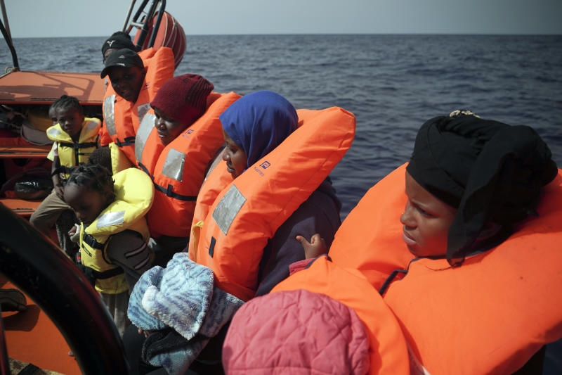 Women and children sit on a rescue boat some 53 nautical miles (98 kilometers) from the coast of Libya in the Mediterranean Sea, Tuesday, Sept. 17, 2019. The humanitarian rescue ship Ocean Viking pulled 48 people from a small and overcrowded wooden boat including a newborn and a pregnant woman.(AP Photo/Renata Brito)
