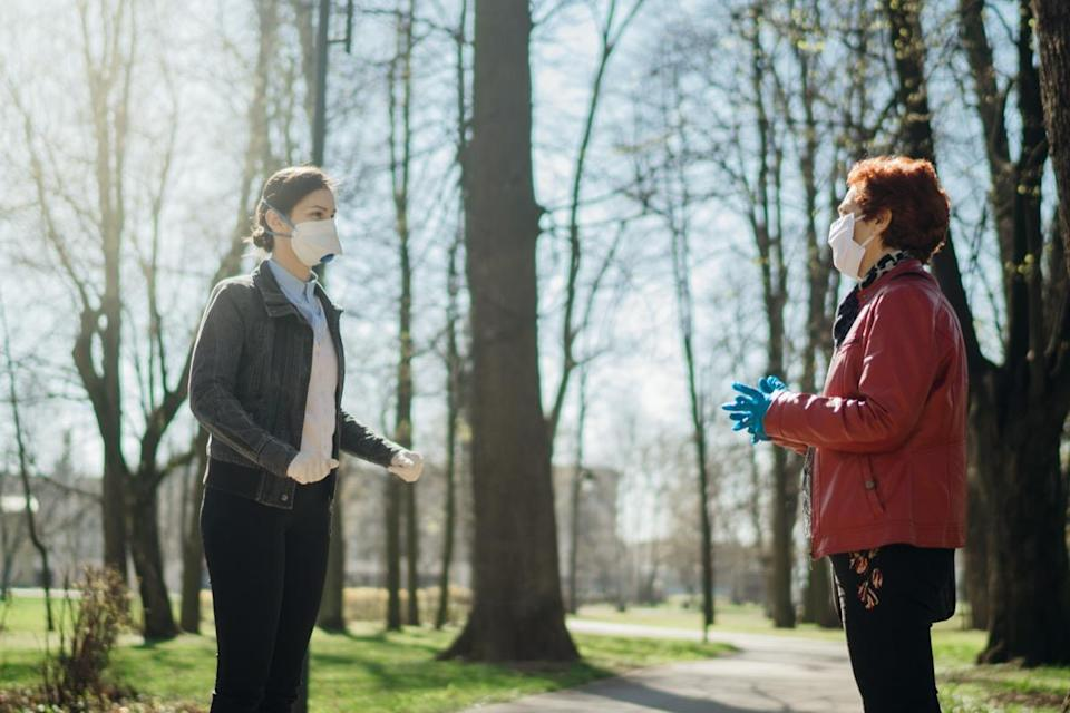 Elderly woman with protective face masks / gloves talking with a friend