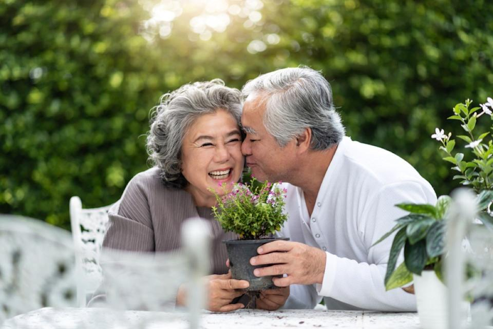older asian man kissing woman on the cheek while holding plant, over 50 regrets