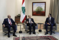 Lebanese President Michel Aoun, center, meets with Prime Minister-Designate Saad Hariri, right, and Lebanese Parliament Speaker Nabih Berri, at the Presidential Palace in Baabda, east of Beirut, Lebanon, Thursday, Oct, 22, 2020. Lebanon's president Michel Aoun asked former premier Saad Hariri to form the country's next government Thursday after he secured enough votes from lawmakers - bringing back an old name to lead the country out of its dire political and economic crises. (Anwar Amro, Pool via AP)
