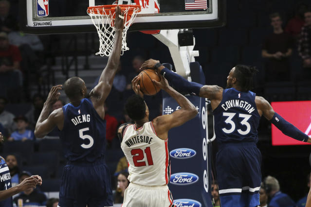 Minnesota Timberwolves' Robert Covington, right, blocks a shot-attempt by Portland Trail Blazers' Hassan Whiteside, center as Timberwolves' Gorgui Dieng, of Senegal, also defends in the first half of an NBA basketball game Thursday, Jan. 9, 2020, in Minneapolis. (AP Photo/Jim Mone)