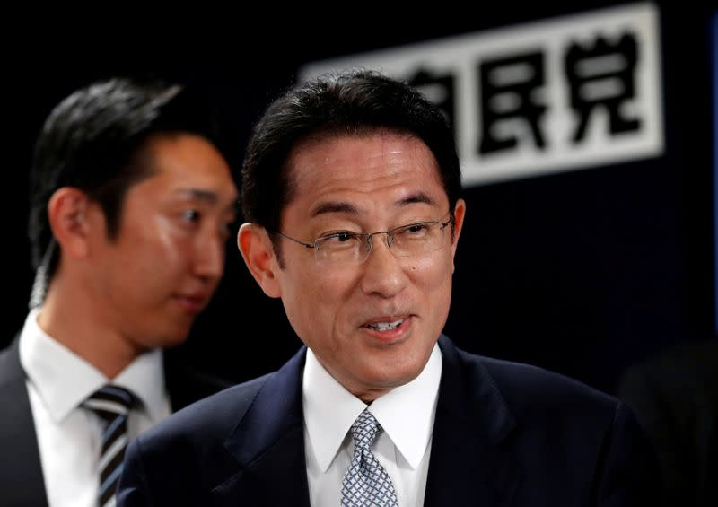 Japan's ruling Liberal Democratic Party policy chief Kishida smiles as he arrives at the LDP headquarters in Tokyo