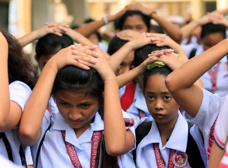 Students use their hands to cover their heads as they evacuate their school premises after an earthquake of magnitude 6.2 hit the northern island of Luzon and was felt in the Metro Manila, Philippines August 11, 2017, shaking buildings and forcing the evacuation of offices and schools. REUTERS/Romeo Ranoco