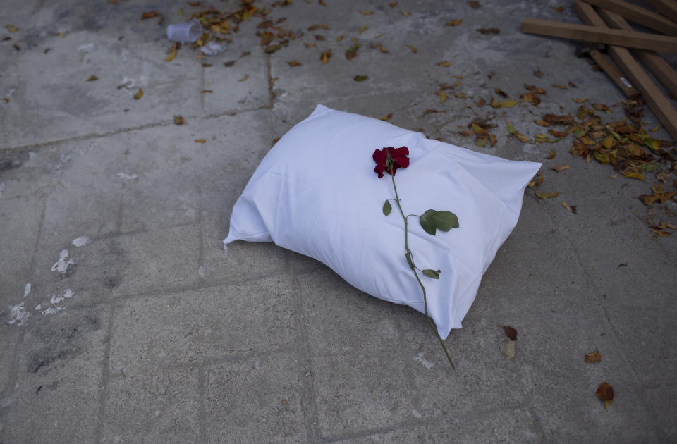 A pillow with a rose sits on the sidewalk during a protest against the Government's handling of the COVID-19 pandemic, organized by the Rio de Paz NGO in front of the Ronaldo Gazolla hospital in Rio de Janeiro, Brazil, Wednesday, March 24, 2021. (AP Photo/Silvia Izquierdo)
