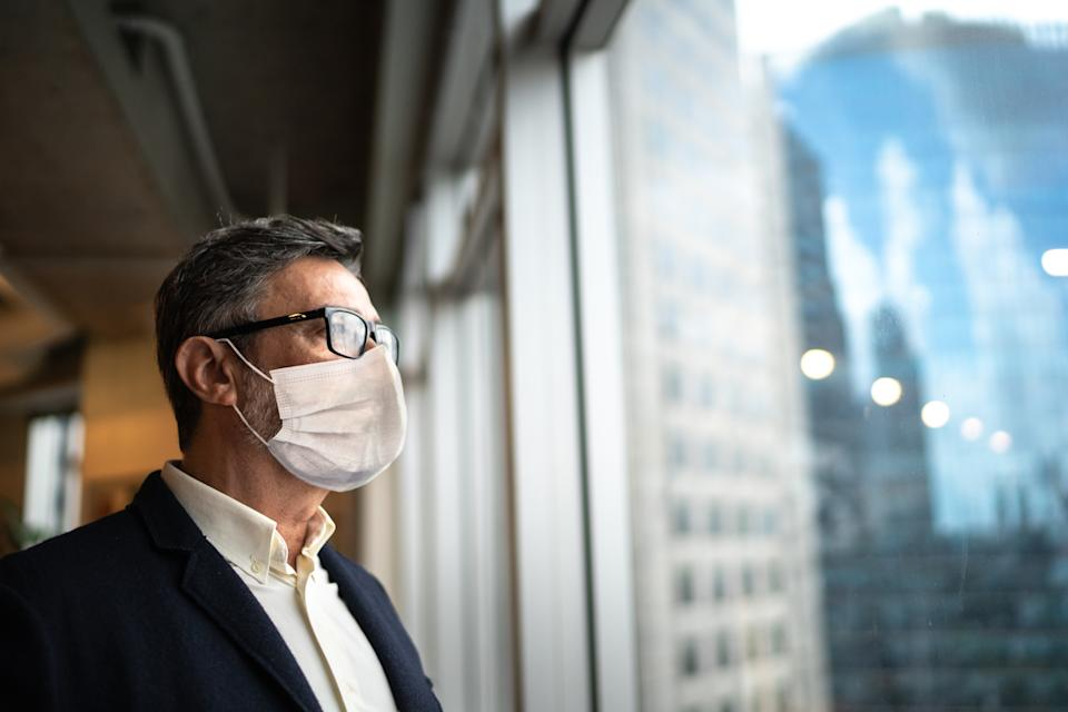 Mature businessman looking out of window with face mask