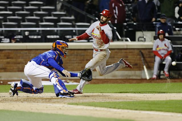 St. Louis Cardinals' Matt Carpenter (13) races to beat the throw to home plate as New York Mets catcher Travis d'Arnaud, left, waits for the ball during the ninth inning of a baseball game on Wednesday, April 23, 2014, in New York. The Mets won the game 3-2. (AP Photo/Frank Franklin II)