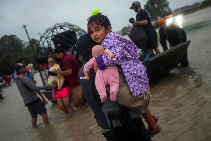 <p>A woman holds a girl as her family arrives to high ground by boat due to floods caused by Tropical Storm Harvey along Tidwell Road in east Houston, Texas, U.S. August 28, 2017. (Photo: Adrees Latif/Reuters) </p>