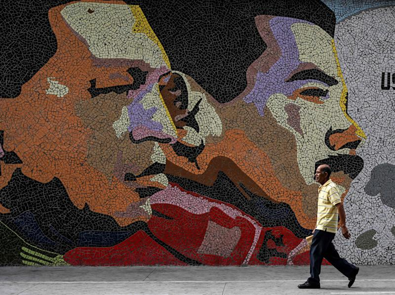 A man walks past a mosaic depicting late Venezuelan President Hugo Chavez (left) and Venezuelan president Nicolas Maduro in Caracas, Venezuela, on January 30, 2019.