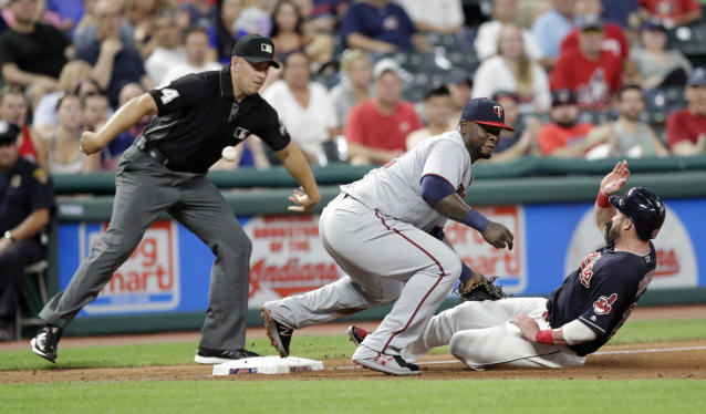 Cleveland Indians' Jason Kipnis slides safely into third base as Minnesota Twins' Miguel Sano lets the ball get by in the sixth inning of a baseball game, Tuesday, Aug. 28, 2018, in Cleveland. Umpire John Libka watches. (AP Photo/Tony Dejak)