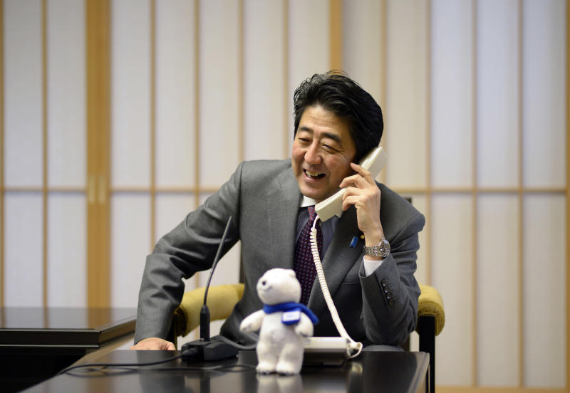 Japanese Prime Minister Shinzo Abe talks to Japan's Yuzuru Hanyu, winner of Sochi Olympics men's figure skating gold medal, on a phone at the prime minister's residence in Tokyo, Saturday, Feb. 15, 2014. Japan celebrated Hanyu's historic win in men's figure skating at the break of dawn Saturday, rejoicing in the country's first-ever gold medal in the Olympic event. (AP Photo/Franck Robichon, Pool)