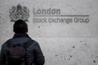FILE PHOTO: A pedestrian in front of the London Stock Exchange offices