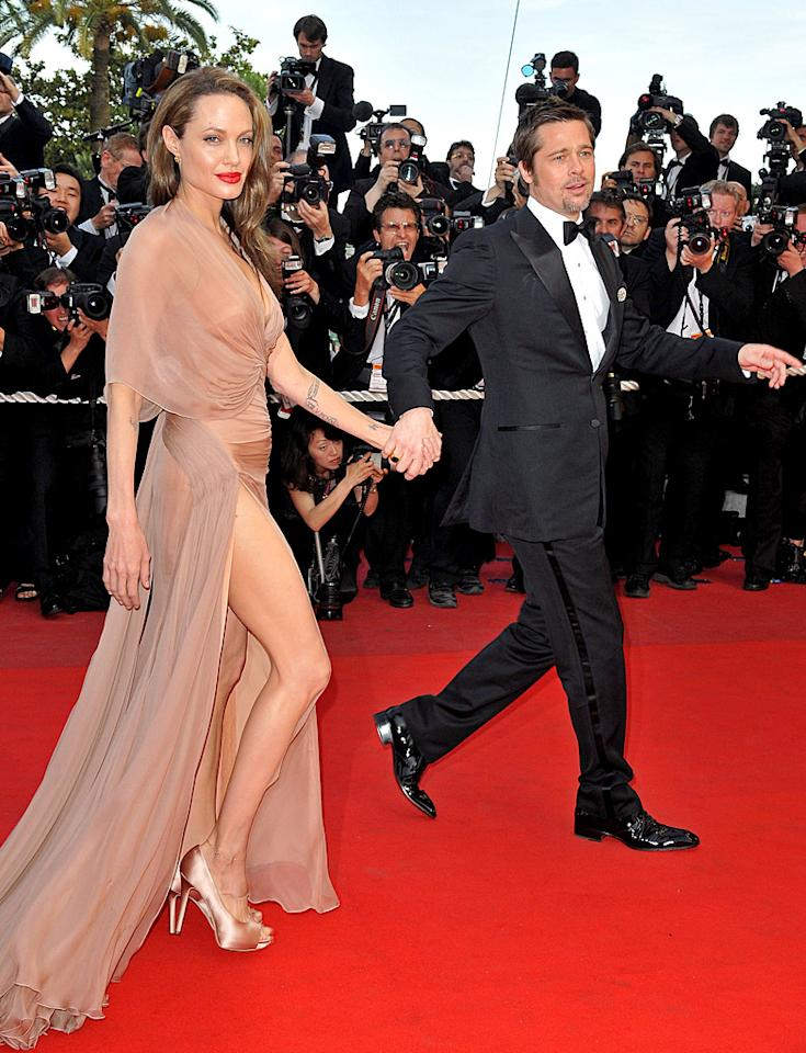 """Angie and her leg were joined by the dashing Brad Pitt as they attended the premiere of his movie """"Inglourious Basterds"""" at the Cannes Film Festival in France a few years ago. They do make a handsome trio, don't they? (5/20/2009)"""