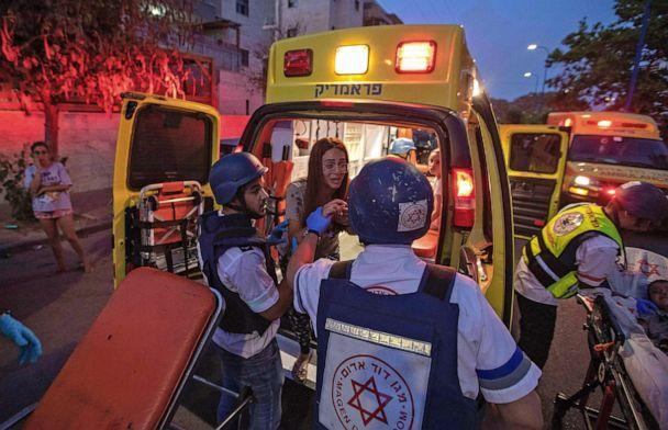 PHOTO: Rescue workers evacuate a woman by ambulance, amidst a rocket attack from the Gaza Strip, in the southern Israeli city of Sderot, May 12, 2021. (Yehuda Perez/AFP via Getty Images)