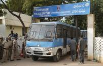 A police van carrying four men accused of the alleged rape and murder of a 27-year-old woman, leaves a police station in Shadnagar