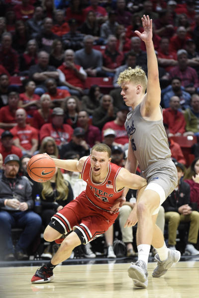 San Diego State guard Malachi Flynn (22) drives past the defense of Nevada forward Zane Meeks (15) during the first half of an NCAA college basketball game Saturday, Jan. 18, 2020, in San Diego. (AP Photo/Denis Poroy)