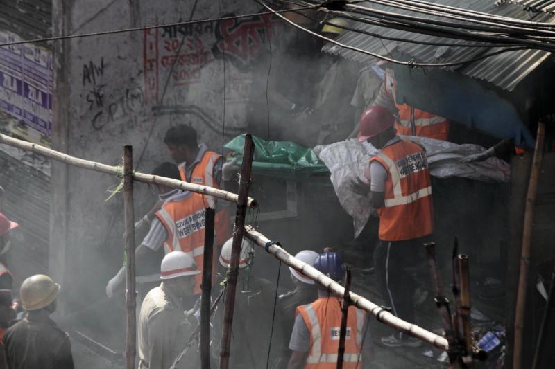 Rescue workers carry a victim's body wrapped in plastic bag after a fire broke out early morning at an illegal six-story plastics market in Kolkata, India, Wednesday, Feb. 27, 2013. More than a dozen people were killed and others were hospitalized in critical condition. (AP Photo/Bikas Das)