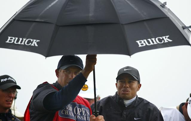 """<h1 class=""""title"""">Tiger Woods, of the USA, grimaces beneath an umbre</h1> <div class=""""caption""""> MUIRFIELD, UNITED KINGDOM: Tiger Woods, of the USA, grimaces beneath an umbrella during a torrential downpour during the third round at The 131st Open Championship at Muirfield, Scotland 20 July 2002. Woods scored a 10 over par round leaving him +6 over par for the tournament. AFP PHOTO Adrian DENNIS (Photo credit should read ADRIAN DENNIS/AFP/Getty Images) </div> <cite class=""""credit"""">ADRIAN DENNIS</cite>"""