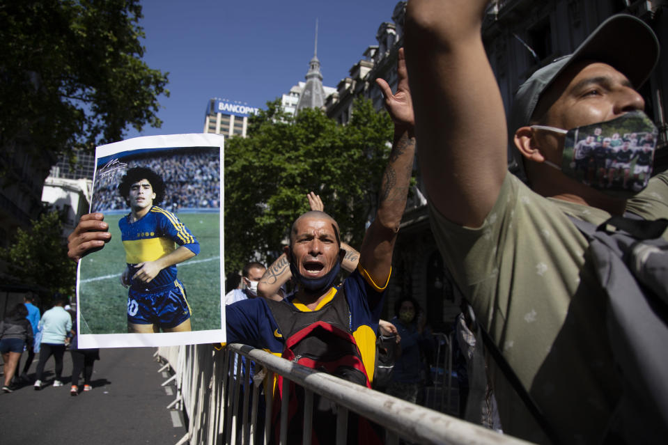 A man holds a poster of Diego Maradona when he played for the soccer club Boca Juniors, as he waits in a line outside the presidential palace to pay his last respects, in Buenos Aires, Argentina, Thursday, Nov. 26, 2020. The Argentine soccer great who was among the best players ever and who led his country to the 1986 World Cup title died from a heart attack at his home Wednesday, at the age of 60. (AP Photo/Maria Paula Avila)