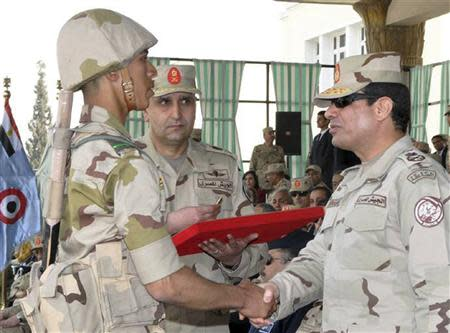 Egypt's army chief Field Marshal Sisi shakes hands with military cadet at end of ceremony to mark end of basic military training preparation period for college students and military academics in Cairo