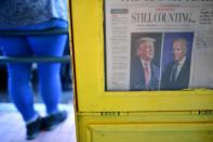 """A newspaper's front headline states """"STILL COUNTING..."""" as activists in celebration after Democratic presidential nominee Joe Biden overtook President Donald Trump in the Pennsylvania general election vote count in Philadelphia"""
