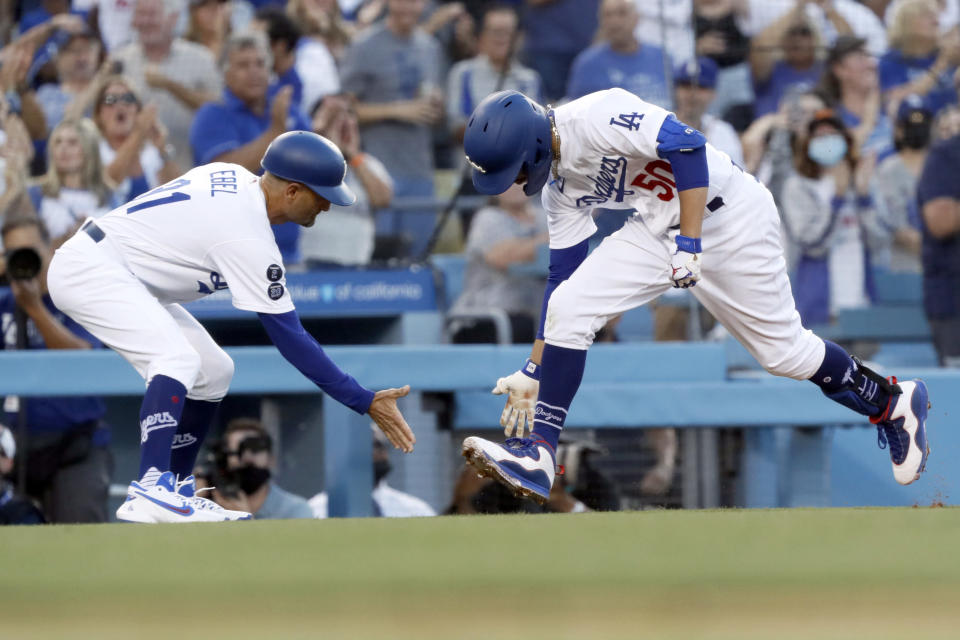 Los Angeles Dodgers' Mookie Betts, right, celebrates with third base coach Dino Ebel while rounding third after hitting a solo home run, his second homer of the baseball game, during the second inning against the Houston Astros in Los Angeles, Wednesday, Aug. 4, 2021. (AP Photo/Alex Gallardo)