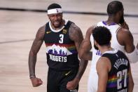 Denver Nuggets' Torrey Craig (3) and Jamal Murray (27) celebrate a dunk by Murray as Los Angeles Lakers' LeBron James, right walks past during the second half of Game 3 of the NBA basketball Western Conference final, Tuesday, Sept. 22, 2020, in Lake Buena Vista, Fla. (AP Photo/Mark J. Terrill)