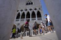 Tourists walks on a bridge in front of Palazzo Ducale, in Venice, Italy, Thursday, June 17, 2021. After a 15-month pause in mass international travel, Venetians are contemplating how to welcome visitors back to the picture-postcard canals and Byzantine backdrops without suffering the indignities of crowds clogging its narrow alleyways, day-trippers perched on stoops to imbibe a panino and hordes of selfie-takers straining for a spot on the Rialto Bridge or in front of St. Mark's Basilica. (AP Photo/Luca Bruno)