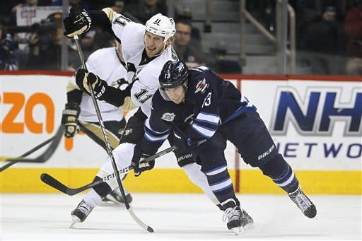 Winnipeg Jets forward Kyle Wellwood (13) and Pittsburgh Penguins forward Jordan Staal (11) fight for position during second-period NHL hockey game action in Winnipeg, Manitoba, Friday, Dec. 23, 2011. (AP Photo/The Canadian Press, John Woods)