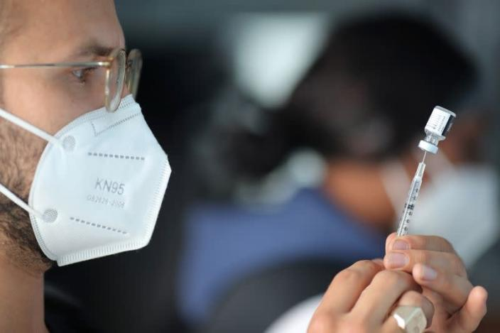 EMT Lenny Fernandez prepares a Pfizer coronavirus disease (COVID-19) vaccination at a mobile vaccination drive for essential food processing workers at Rose & Shore, Inc., in Vernon, Los Angeles
