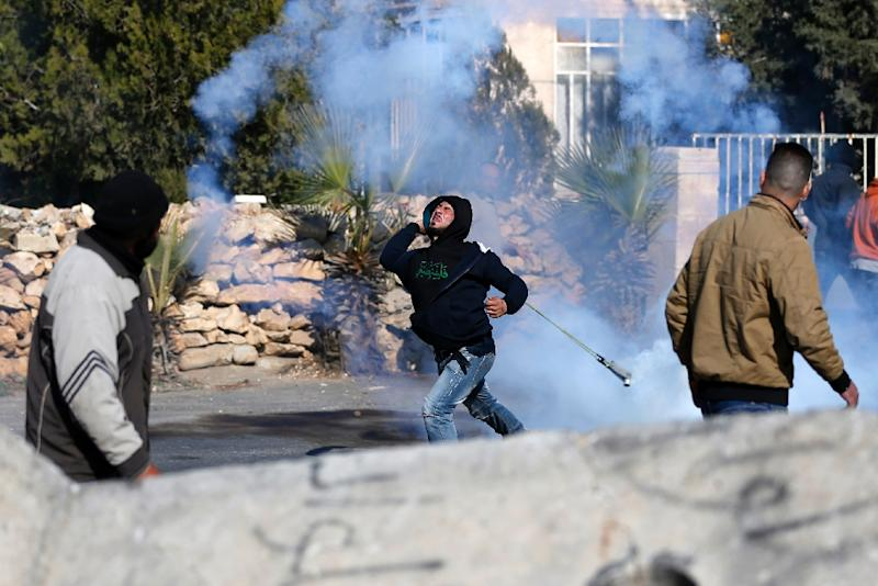 A Palestinian protester throws back a tear gas canister with a slingshot in clashes with Israeli security forces on December 11, 2015 in the occupied West Bank (AFP Photo/Abbas Momani)